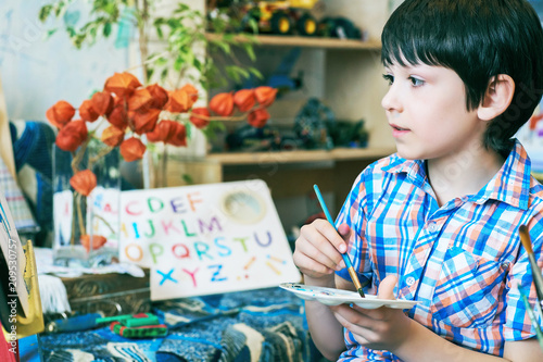 Foto Murales Young boy sitting in front of easel painting a fish, holding a brush in hand. Boy is getting ready to become an artist.