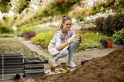 Foto Murales Young woman working in flower garden