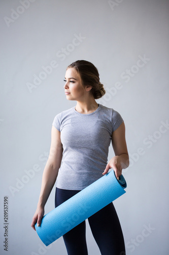 Attractive beautiful young sportswoman holding yoga mat isolated over grey.