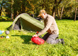 elderly tourist foldjng a tent in the forest