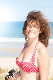 Laughing woman in swimsuit on the beach on a sunny day