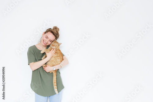 portrait handsome young hipster woman, hugs his good friend ginger cat on white wall background. Positive human emotions, facial expression, feelings. People and animals in love