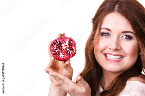 Cheerful woman holds pomegranate fruits, isolated
