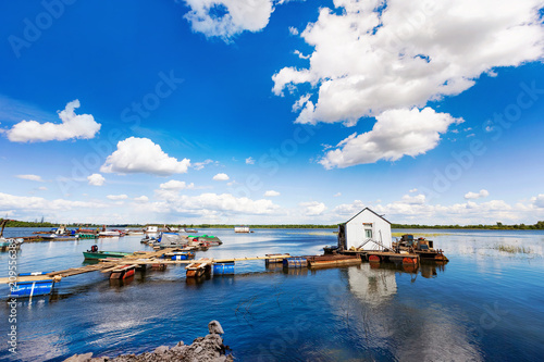 Foto Murales Summer sunny waterscape of rural river pier with cloudy sky background.