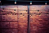 garlands with electric bulbs abstractly light the vintage room with a brick wall - 209556732