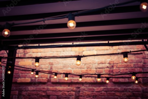garlands with electric lamps abstractly light the vintage room with a brick wall