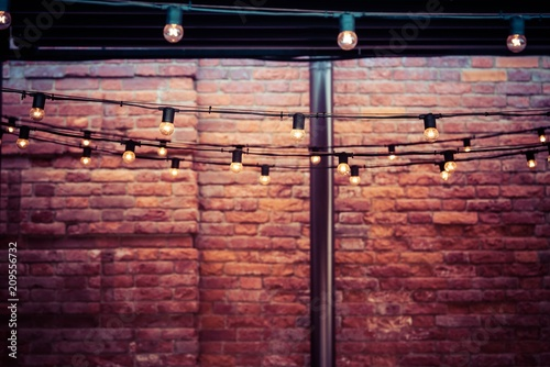 garlands with electric bulbs abstractly light the vintage room with a brick wall