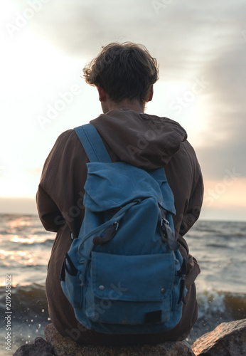 Fotobehang Skateboard Hipster man with backpack sitting on the seashore. View from back.