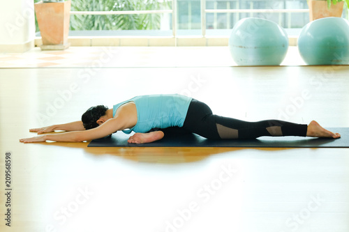 Plakat Young asian woman practicing yoga, fitness stretching flexibility pose, working out, healthy lifestyle, wellness, well being