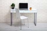 White table near the white wall. Empty workplace in the room. White background. - 209570754