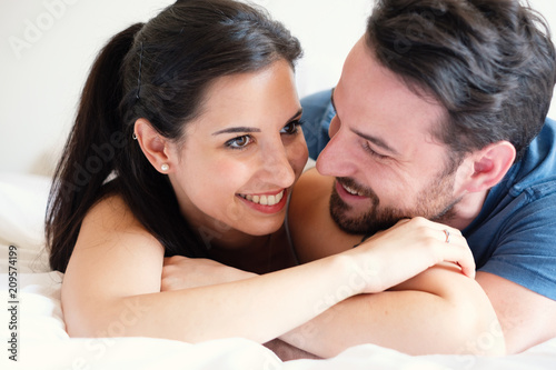 Leinwanddruck Bild Love couple lying in bed kissing and looking each other