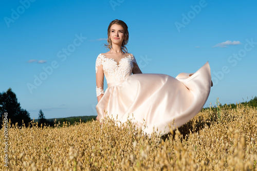 Foto Murales charming girl in beautiful beige dress in field rye