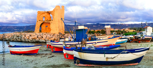 Plexiglas Freesurf Picturesque old harbour with tradtional fishing boats and saracen tower over sunset.