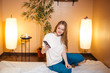 Leinwanddruck Bild - Cute young blonde woman using a smartphone while waiting massage at spa sitting in a cozy room with torchers