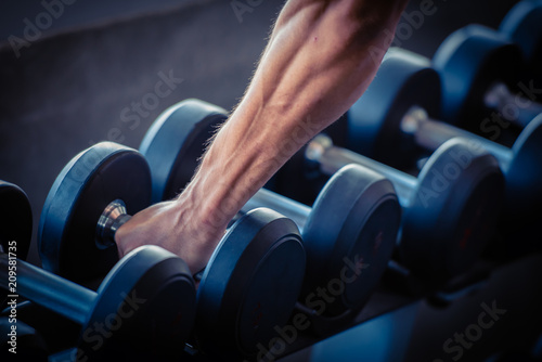 Wall mural Strong bodybuilder man lifting weights in the sport gym, close up ,bodybuilding and muscle building concept.