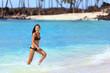 Hawaii beach vacation Asian bikini woman having fun splashing water waves in blue ocean at tropical travel destination. Young girl in black swimsuit playing in sea.