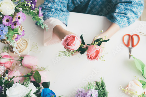 Female hands making beautiful flower composition in floral shop.