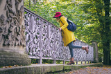 Beautiful woman is wearing woolen coat and red hat. Tourist woman standing on bridge in public park at autumn  - 209588518