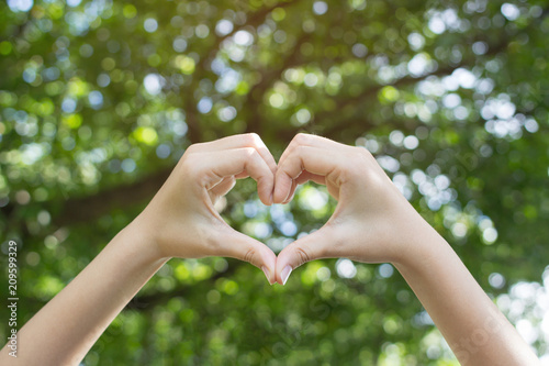 Leinwanddruck Bild close up focus on hands girl make love shape sign for healthy good life concept