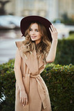 Fashionable beautiful and sensual blonde model girl in sleeveless coat adjusting her stylish hat, smiling and posing outdoors at the city street - 209599930