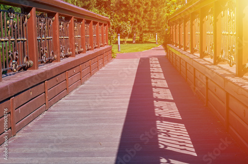 Fotobehang Rood traf. old wooden bridge in the park, natural background with sunlight.