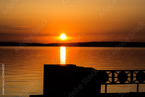 Aluminium Oranje eclat Orange sky from the sunset on the shore of the lake