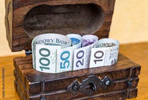 Vintage drewniane pudełko pełne pieniędzy: zwinięte polskich banknotów złotowych w skrzyni na powierzchni drewnianych. Pojęcie osobistych oszczędności przechowywanych w gotówce w domu i gromadzących na emeryturę