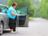 Disabled woman upgoing from a car. Transportation and travel for handicapped people. - 209616909