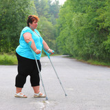 Overweight patient with crutches walking on footpath. Physiotherapy treatment and obesity problems. - 209616939
