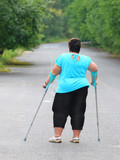 Overweight patient with crutches walking on footpath. Physiotherapy treatment and obesity problems. - 209616960