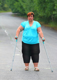 Overweight patient with crutches walking on footpath. Physiotherapy treatment and obesity problems. - 209616973