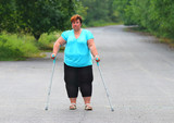 Overweight patient with crutches walking on footpath. Physiotherapy treatment and obesity problems. - 209616988