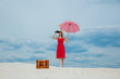 Leinwanddruck Bild - Young woman in red dress with umbrella and suitcase looking in binoculars on the beach. Travel concept image on sand