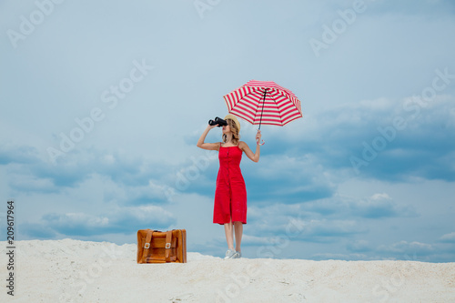 Leinwanddruck Bild Young woman in red dress with umbrella and suitcase looking in binoculars on the beach. Travel concept image on sand