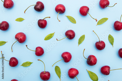 Leinwanddruck Bild background of cherries and leaves on blue