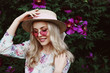 Outdoor close up portrait of beautiful young happy smiling woman with long blonde hair, wearing pink sunglasses, straw hat, dress posing in the blooming garden.  Female spring fashion concept
