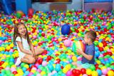 Cute children playing among plastic balls - 209627324