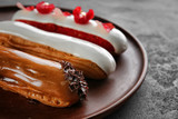 Various tasty eclairs on tray - 209627559