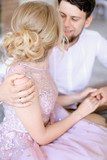 Young blonde bride sitting near happy groom and holding hands. Concept of gladden married couple and wedding. - 209639348