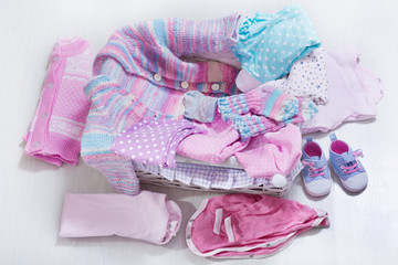 various baby clothes in a box, top view