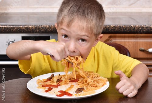 The boy is eating pasta. Proper nutrition. A hungry child. - 209644592