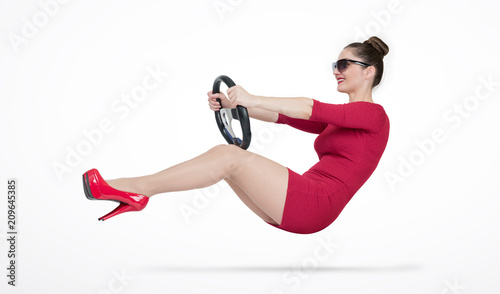 Young girl in red dress and sunglasses is driving a car steering wheel, auto concept