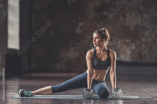 Wall mural Young athletic girl with dumbbells indoors