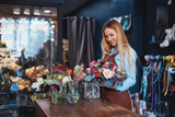 Smiling florist with bouquet indoors