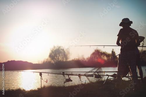 Foto Murales Fishing as recreation and sports displayed by fisherman at lake