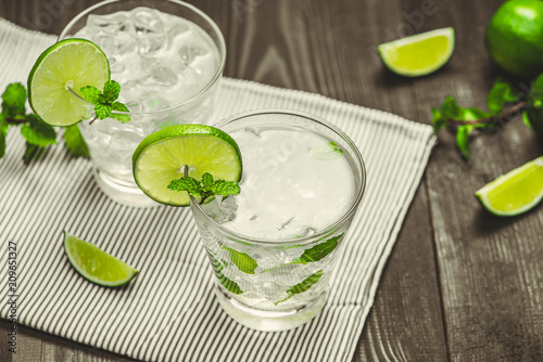 Fresh lime cocktail with ice cubes on wooden background