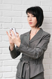 business woman dressed in a gray suit taking selfie on smartphone or preparing to online broadcasting, stay in front of a white wall - 209655395