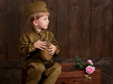 children boy are dressed as soldier in retro military uniforms with flask sitting on old suitcase, dark wood background, retro style - 209655948