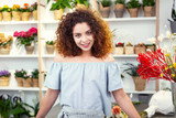 Positive mood. Pleasant cheerful woman looking at you while leaning on the counter in the flower shop - 209656109