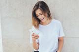 junge frau lacht und schaut auf ihr smartphone - 209656386